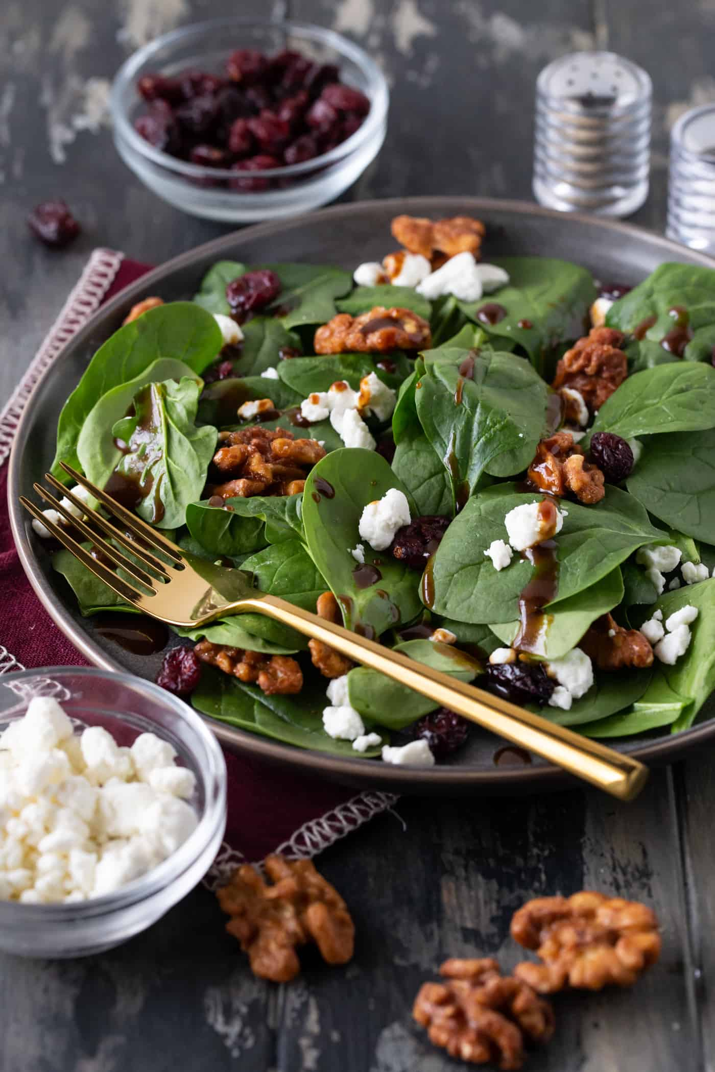 Spinach Salad with Goat Cheese, Craisins and Balsamic Vinaigrette on a grey plate with gold silverware.