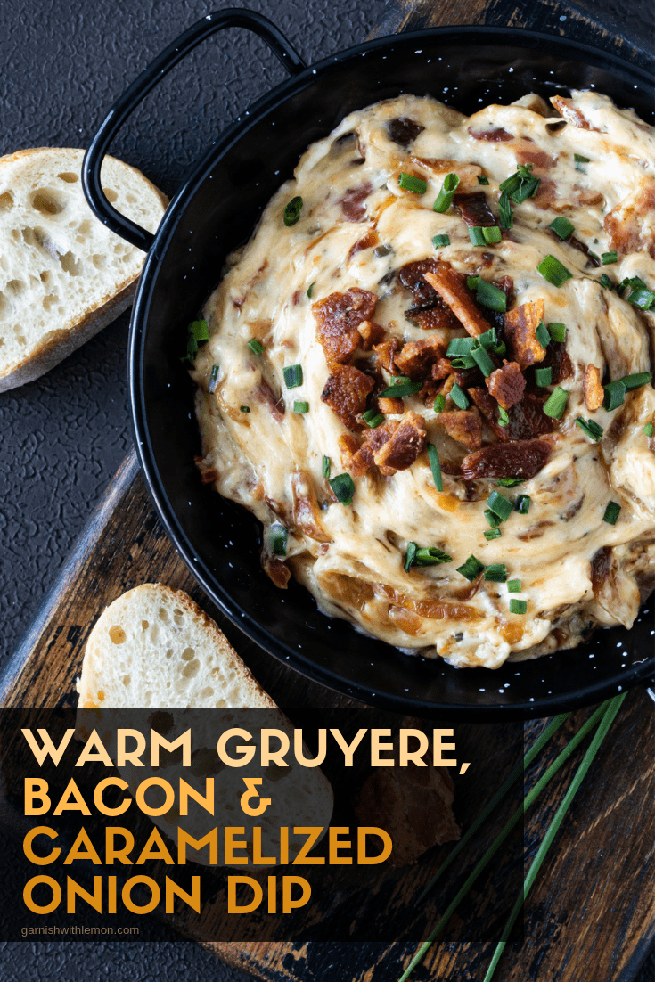 Pinterest image of Warm Gruyere, Bacon and Caramelized Onion Dip on a dark background with chopped bacon and fresh chives for garnish on a dark background.