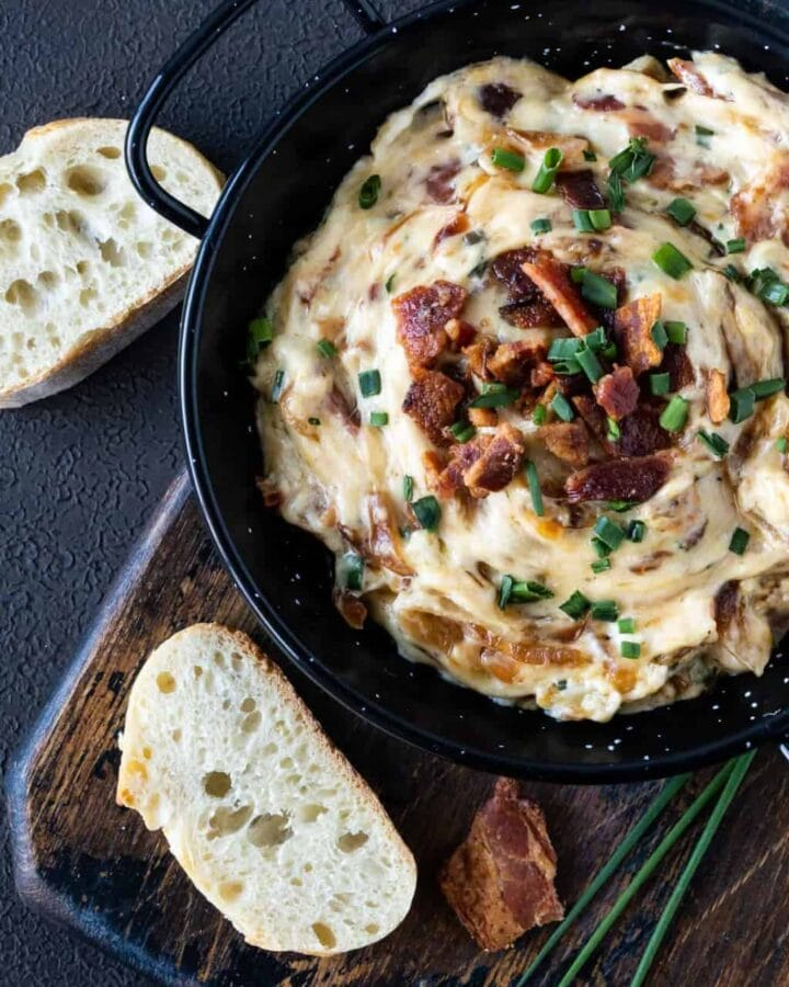 Top down image of Warm Gruyere, Bacon and Caramelized dip on a dark background with chopped bacon and chives for garnish.