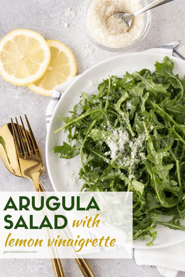Top down image of Arugula Salad with Lemon Vinaigrette Dressing in a white bowl with lemon slice and fresh parmesan for garnish.