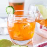 Straight on image of Aperol Gin Cocktail in low ball glass on white background with small cucumber slice for garnish.