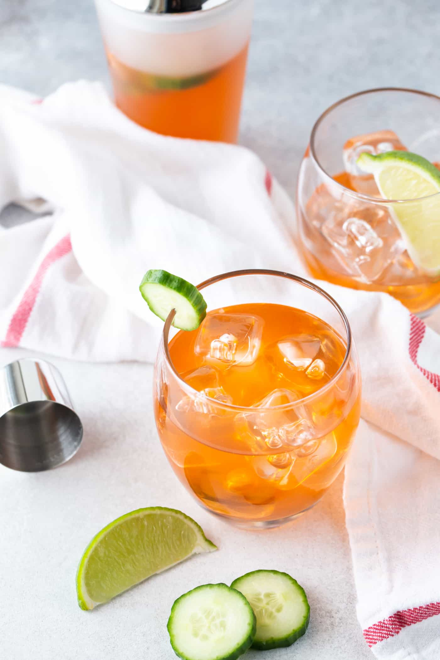 Top down image of Aperol Gin Cocktails on a white background with fresh lime wedges for garnish.
