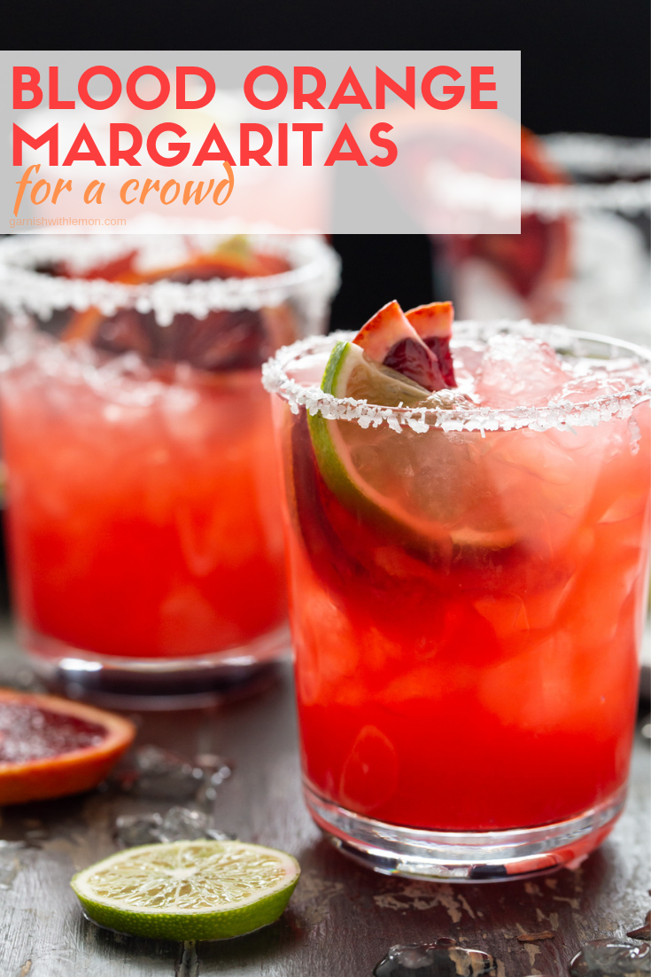 Lowball glasses filled with Blood Orange Margaritas and garnished with fresh slices of blood oranges and limes.