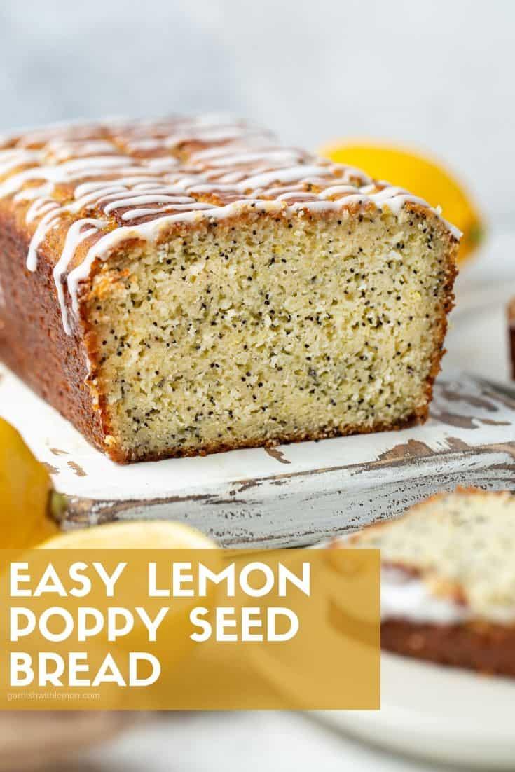 Glazed loaf of lemon poppy seed bread on a white cutting board