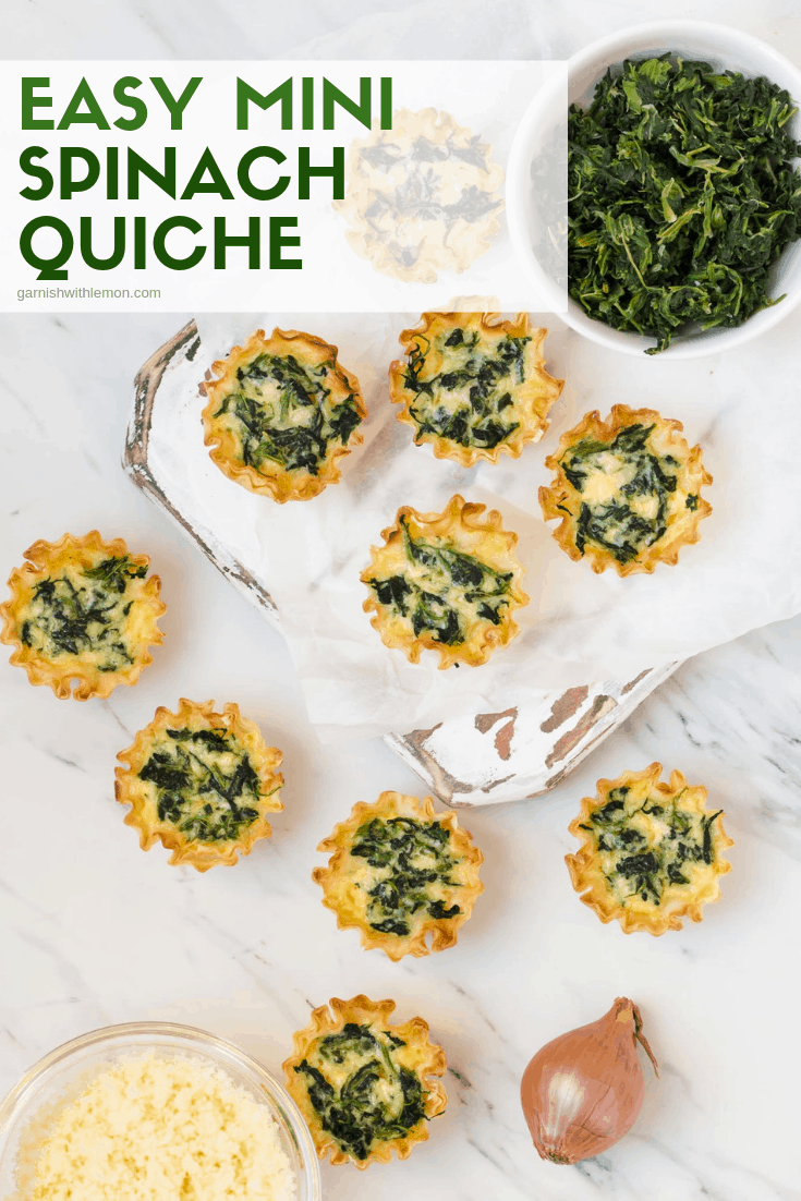 Mini spinach quiche on a distressed white wood board. Garnished with spinach and grated cheese.
