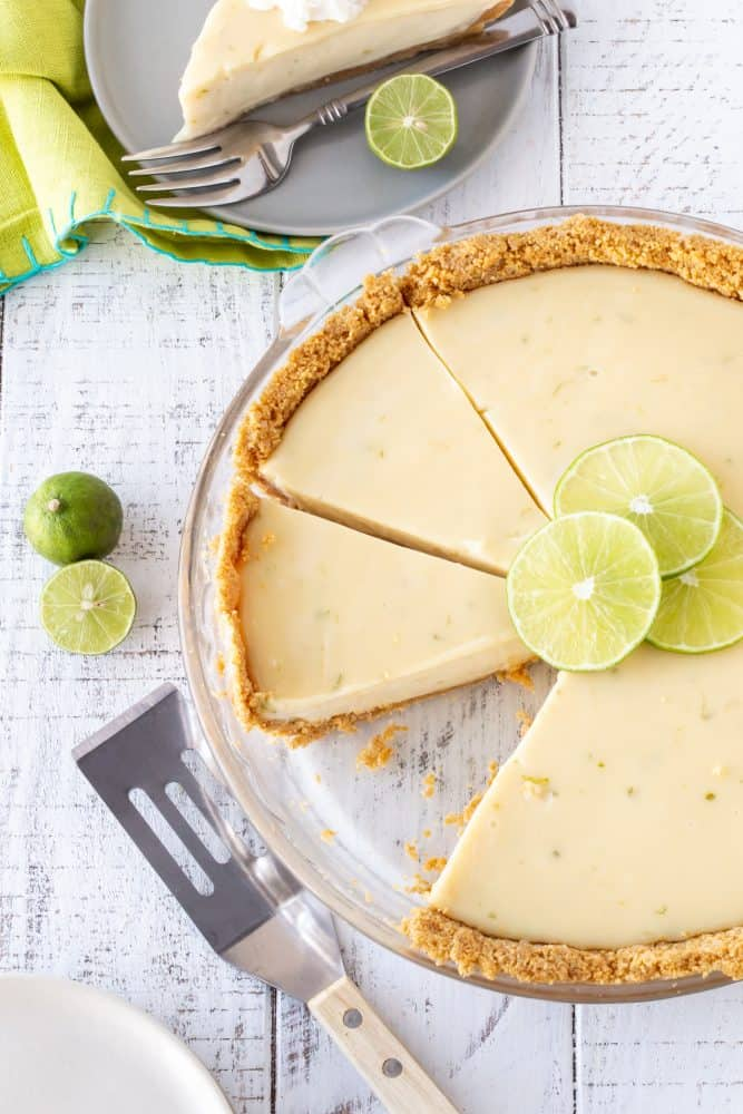 sliced key lime pie in a glass pie plate with fresh lime slices for garnish.