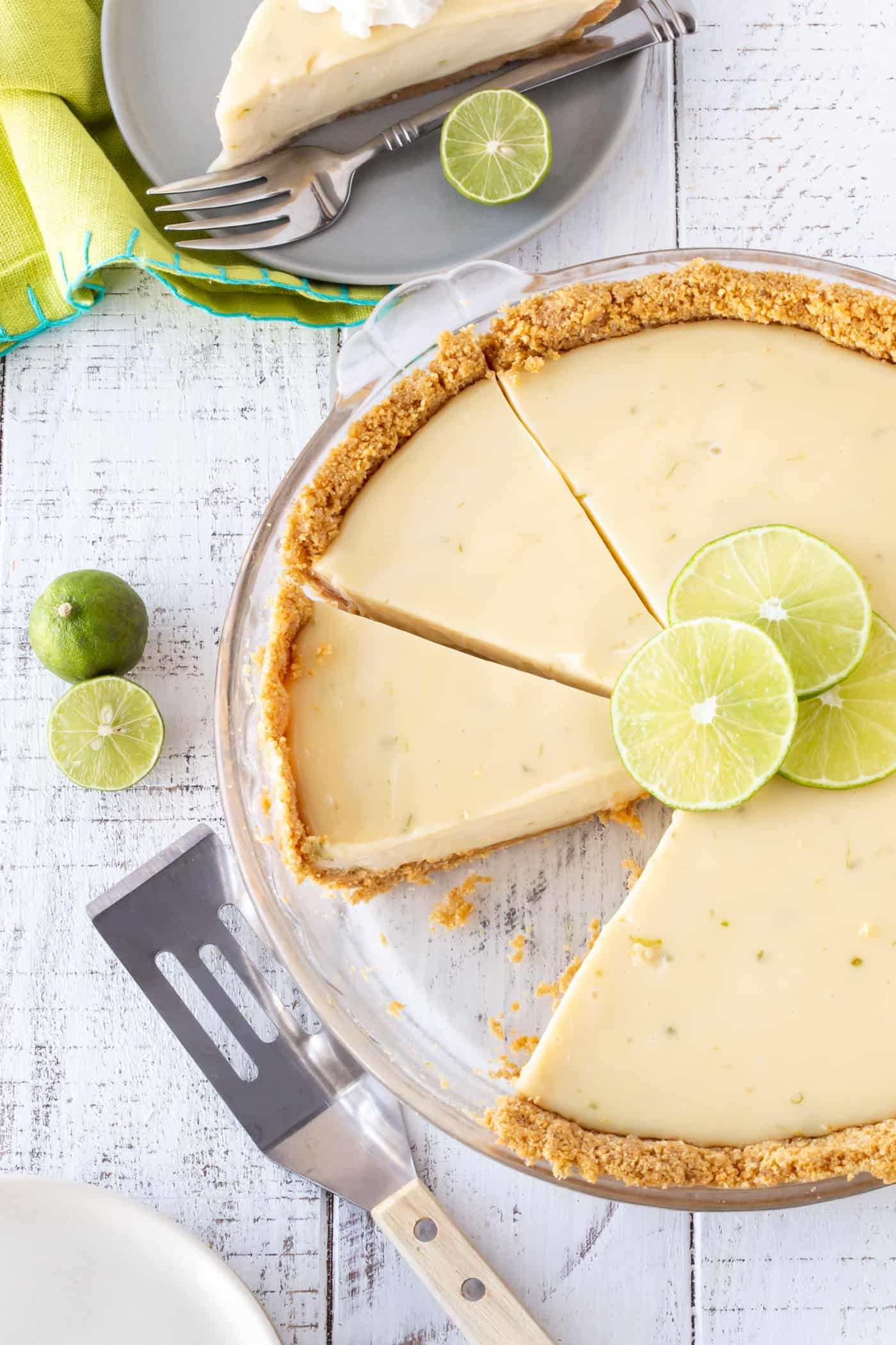 Top down image of sliced key lime pie in a glass pie plate with fresh lime slices for garnish.