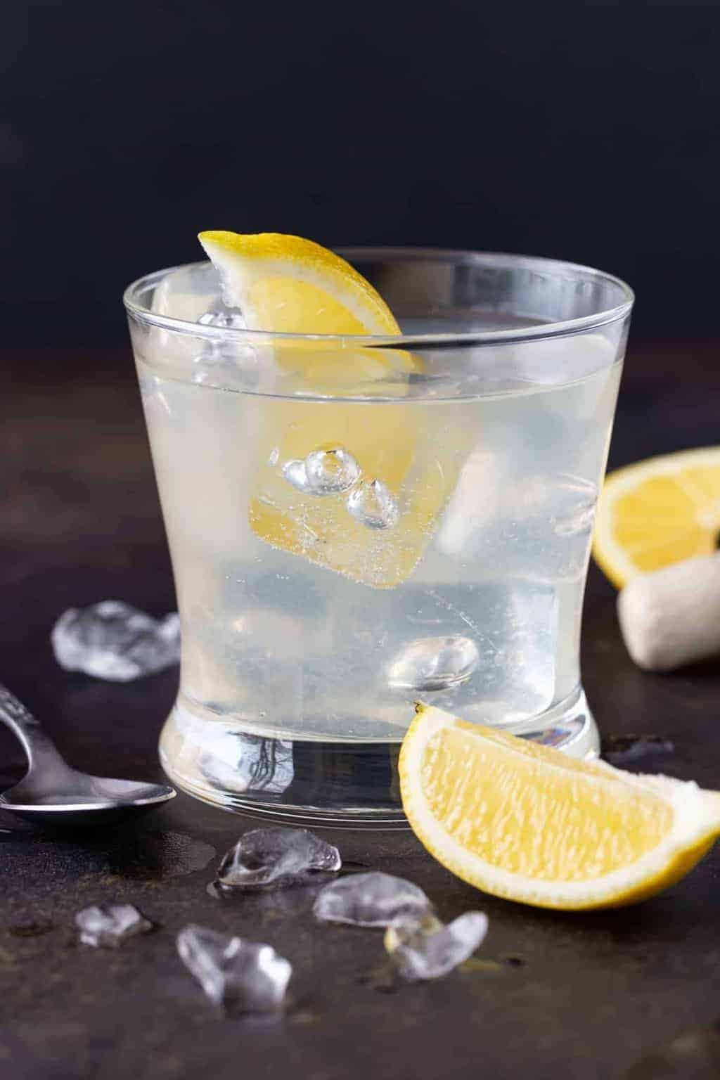 Lowball glass filled with Elderflower Vodka Soda recipe. Garnished with fresh lemon wedges.