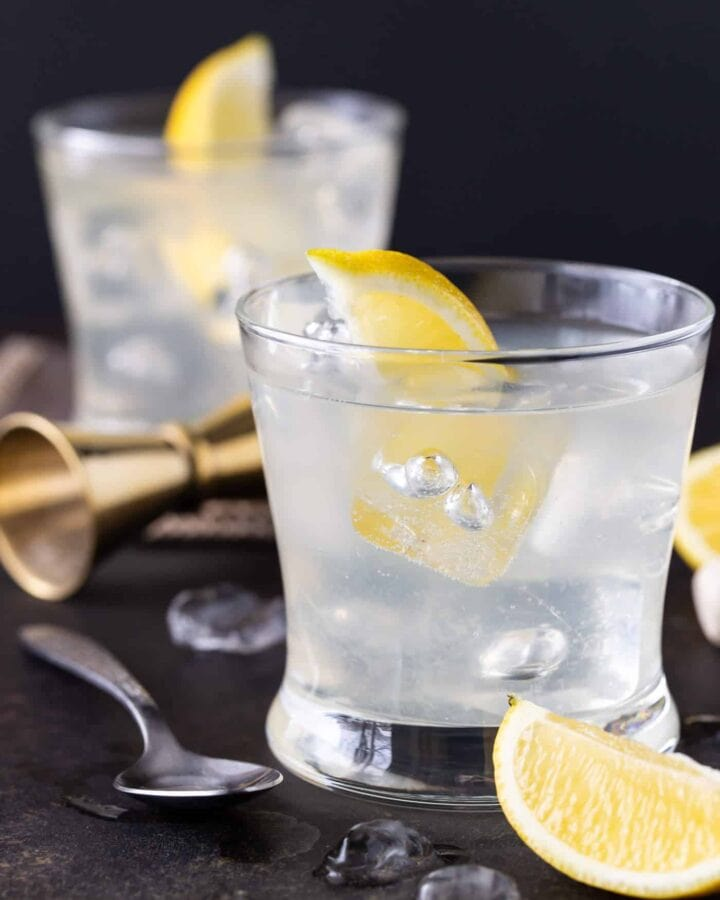 Vodka Soda in two lowball glasses filled with ice. Garnished with lemon wedges.