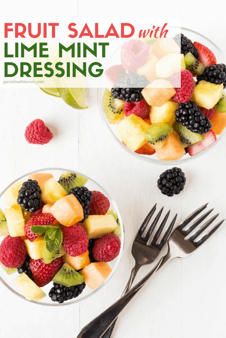 Fruit Salad with Lime mint dressing in glass bowls garnished with fresh mint.