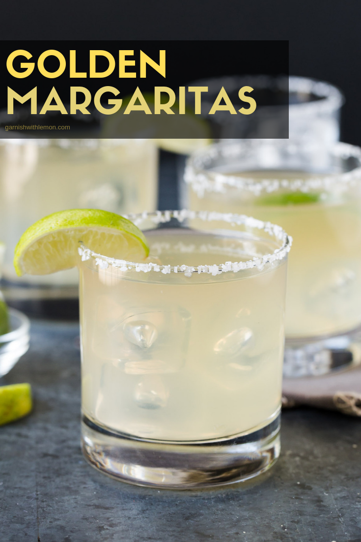 Straight on image of golden margarita on the rocks in a low ball glass with a salted rim.