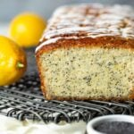 Loaf of lemon poppy seed bread drizzled with glaze on a cooling rack