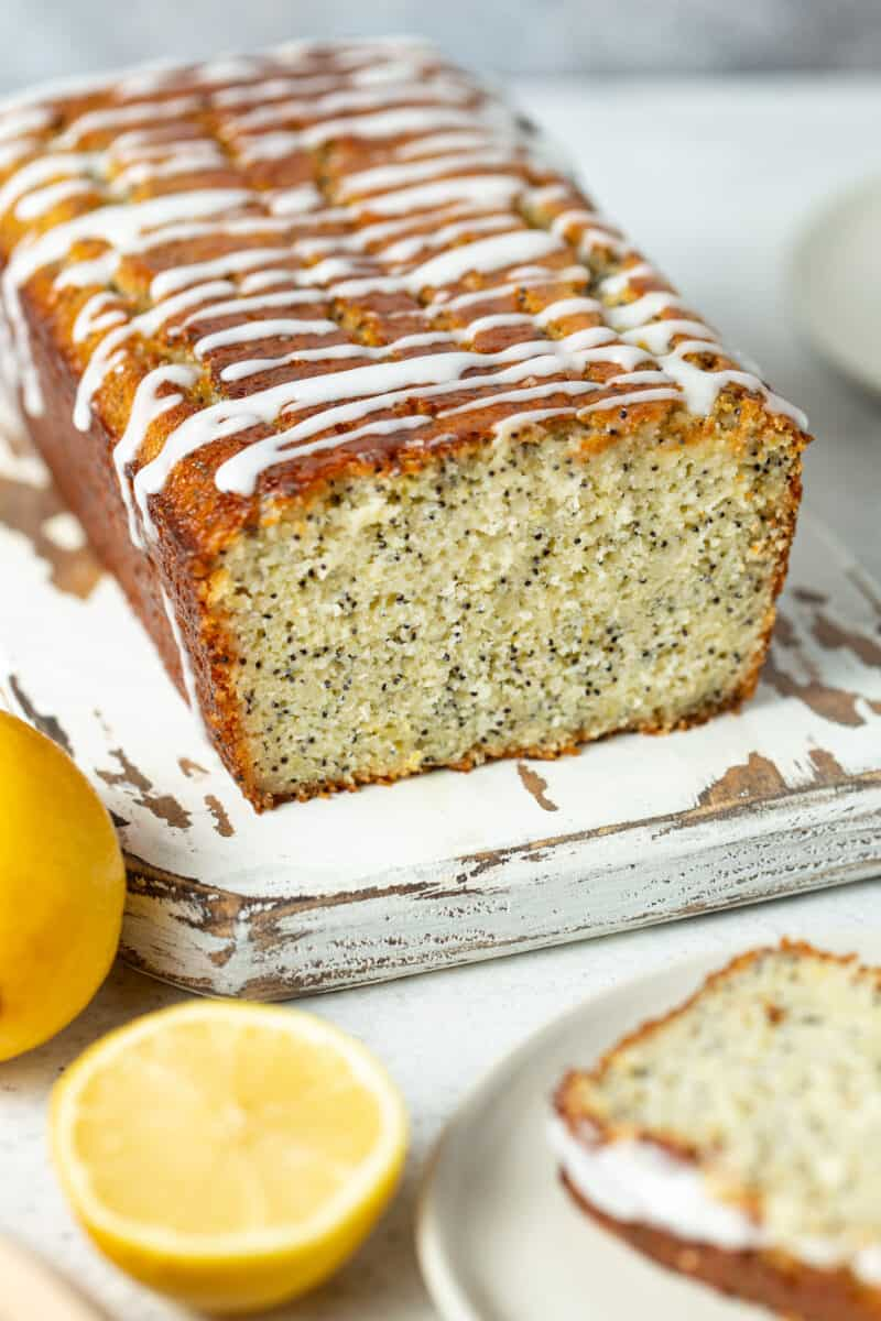 Loaf of lemon poppy seed bread on a white wooden cutting board