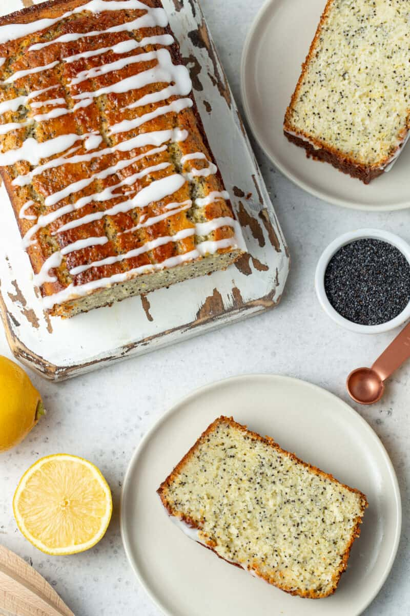 Slices of lemon poppy seed bread on white plates. Loaf on lemon poppy seed bread on a white wooden cutting board.