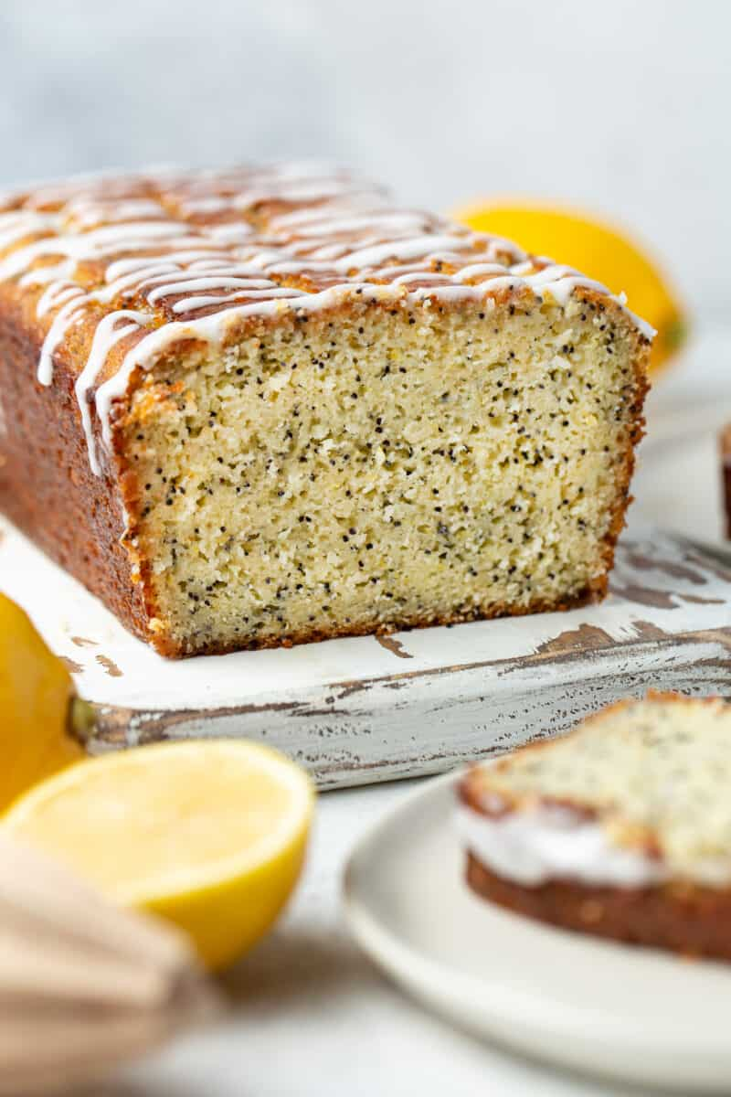 A loaf of lemon poppy seed bread drizzled with a powdered sugar glaze.