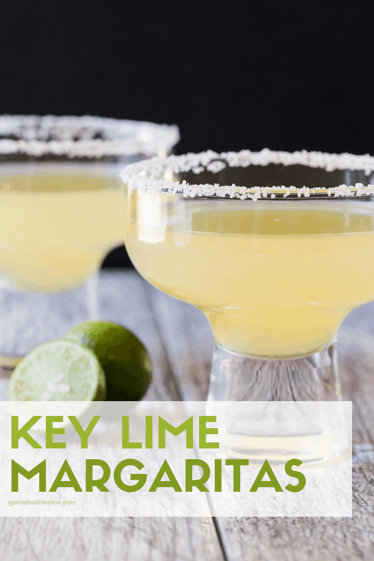 Straight on image of 2 Key lime margaritas in short margarita glasses rimmed with salt and fresh lime for garnish.
