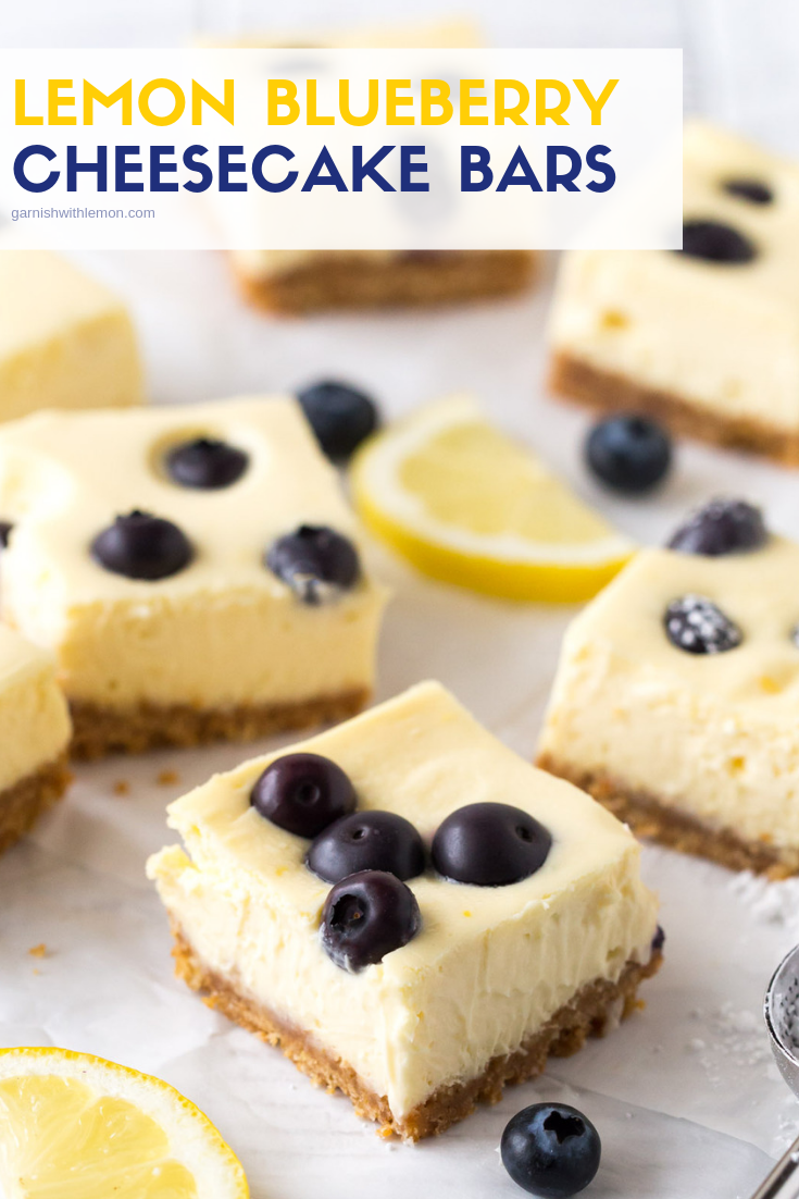 Top down image of cut Lemon Blueberry Cheesecake Bars on a white surface garnished with fresh lemon slices and blueberries.