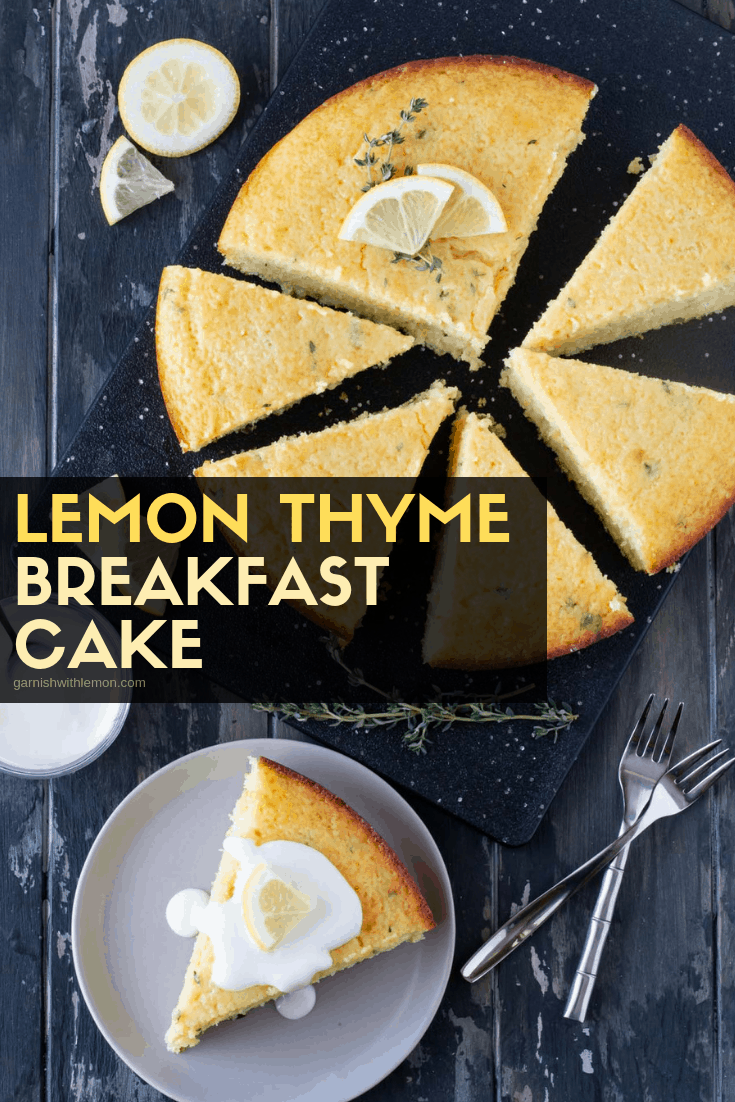 Slices of Lemon Thyme Breakfast Cake on a dark board. Drizzled with icing and garnished with lemon slices and fresh thyme.