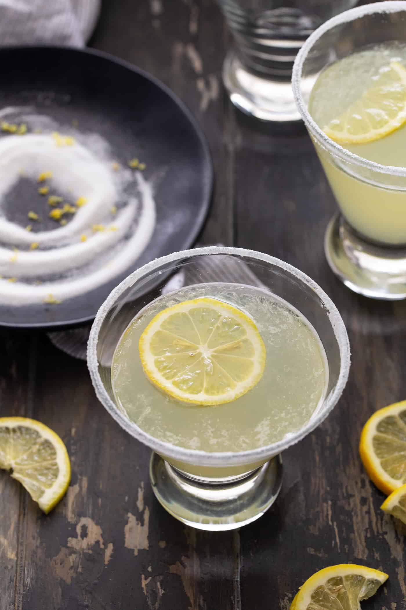 Lemon Drop Martini recipe in a low martini glass with a sugared rim and garnished with a fresh lemon wheel.