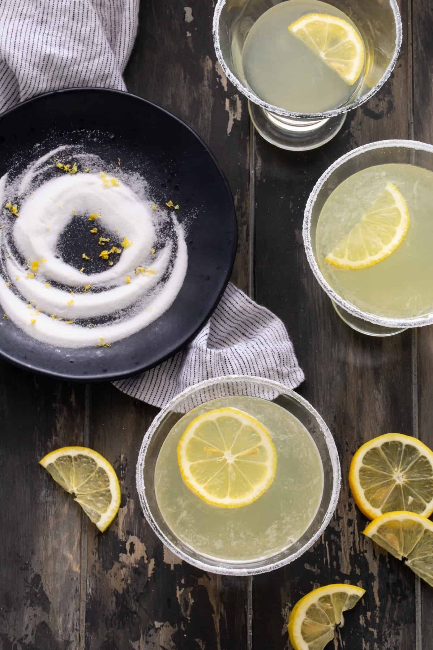 TOp down image of Lemon Drop martini recipe in several low martini glasses with sugared rims and garnished with fresh lemon wheels.