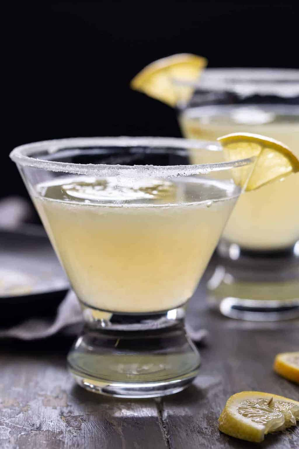 Lemon Drop Martini recipe in a low martini glass with a sugared rim and half of a lemon wedge for a garnish.