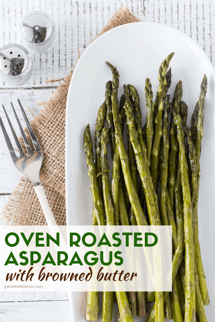 Top down image of Oven Roasted Asparagus on an oval white platter with a fork for serving and a mini salt and pepper shaker on a white wooden background with burlap.