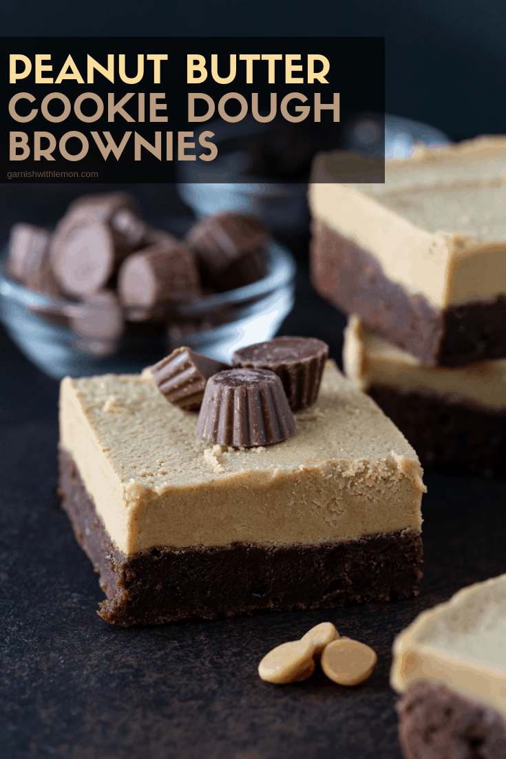 Straight on image of a single Peanut Butter Cookie dough Brownie garnished with mini peanut butter cups with peanut butter chips and additional brownies in background on a warm, dark background.