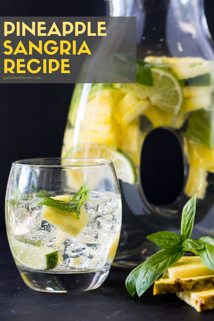 Pitcher of Pineapple Sangria recipe with a glass of sangria garnished with fresh pineapple and basil.