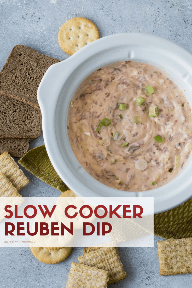 Top down image of Slow Cooker Reuben Dip in a white slow cooker with rye bread for dipping.