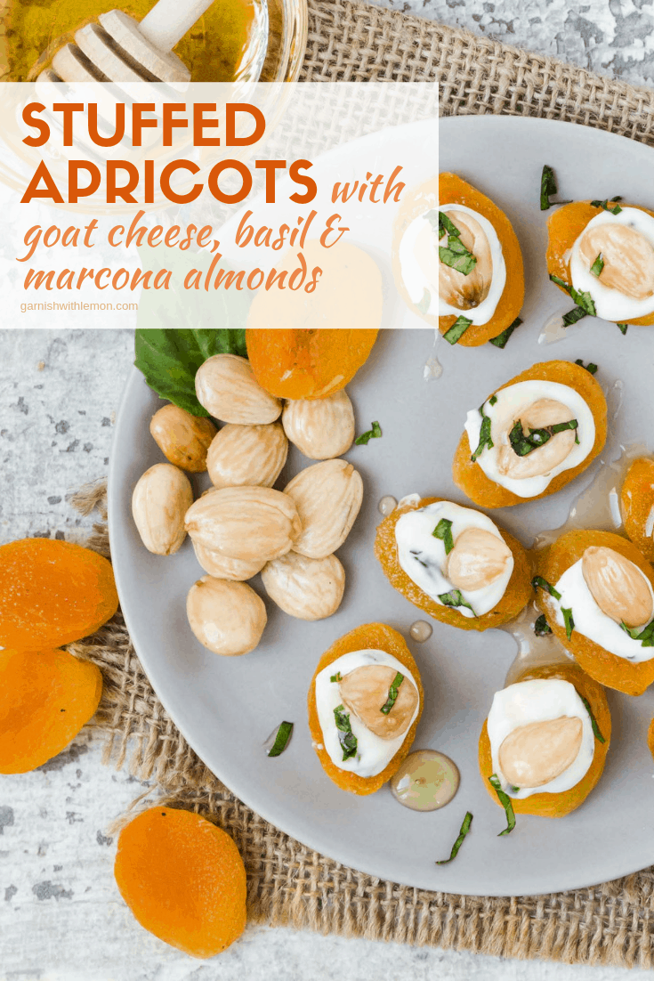 Top down image of Stuffed Apricots with goat cheese, basil and marcona almonds on a gray plate with marcona almonds and apricots for garnish.