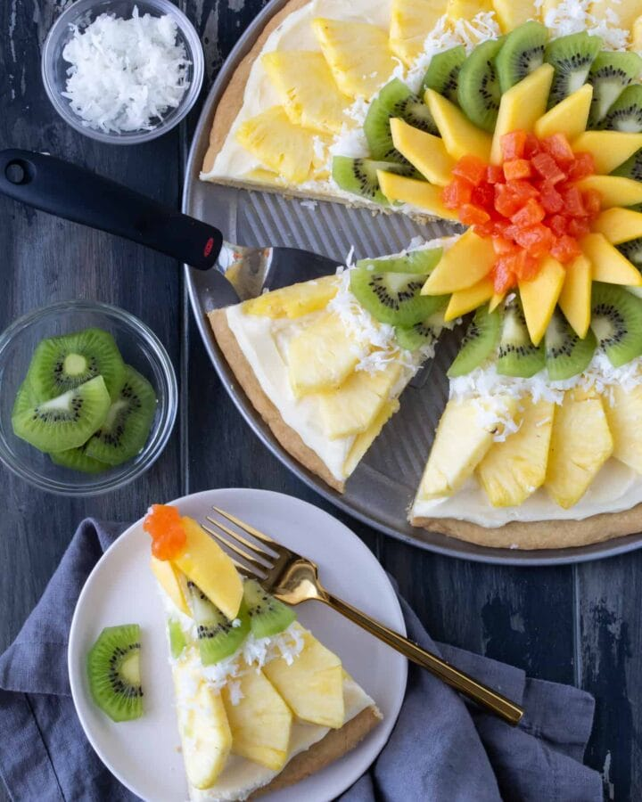 Tropical fruit pizza with pineapple, mango, kiwi and papaya on a sugar cookie crust with a coconut cream cheese frosting.