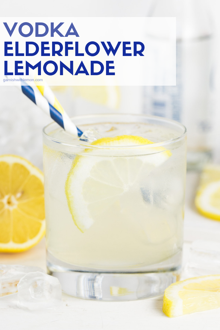 Straight on image of Vodka Elderflower Lemonade in a low ball glass garnished with a fresh lemon slice and a striped straw on a light background