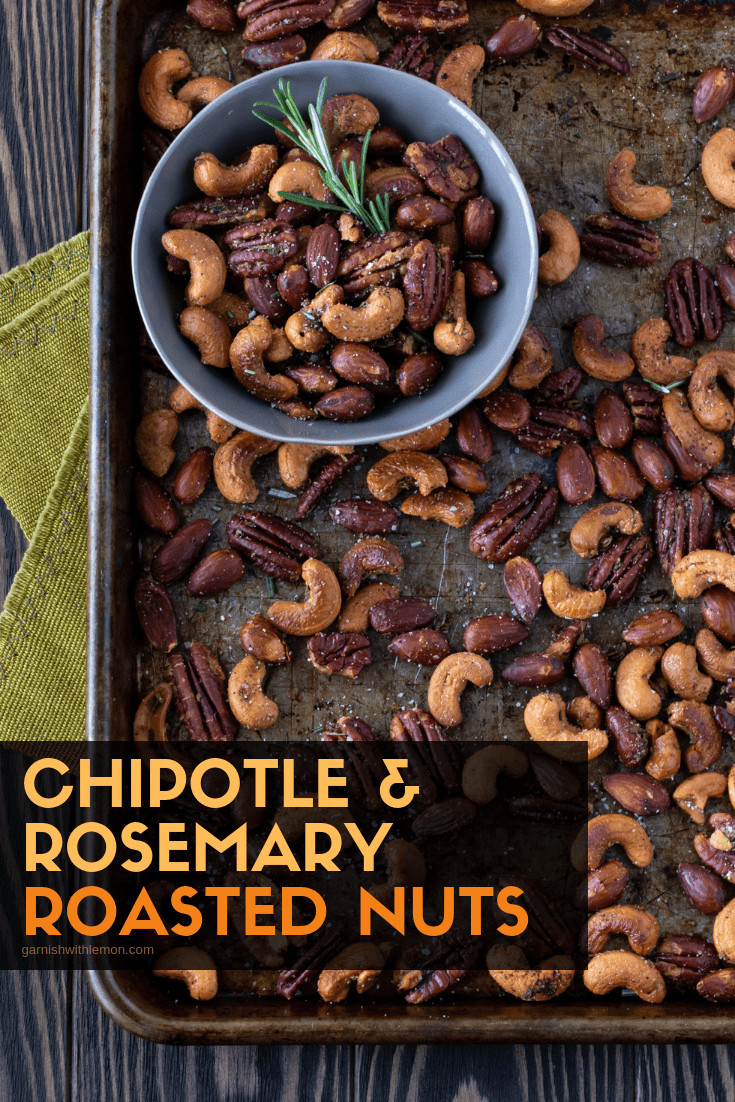 Nuts on s sheet pan with a small bowl of roasted nuts that is garnished with fresh rosemary.