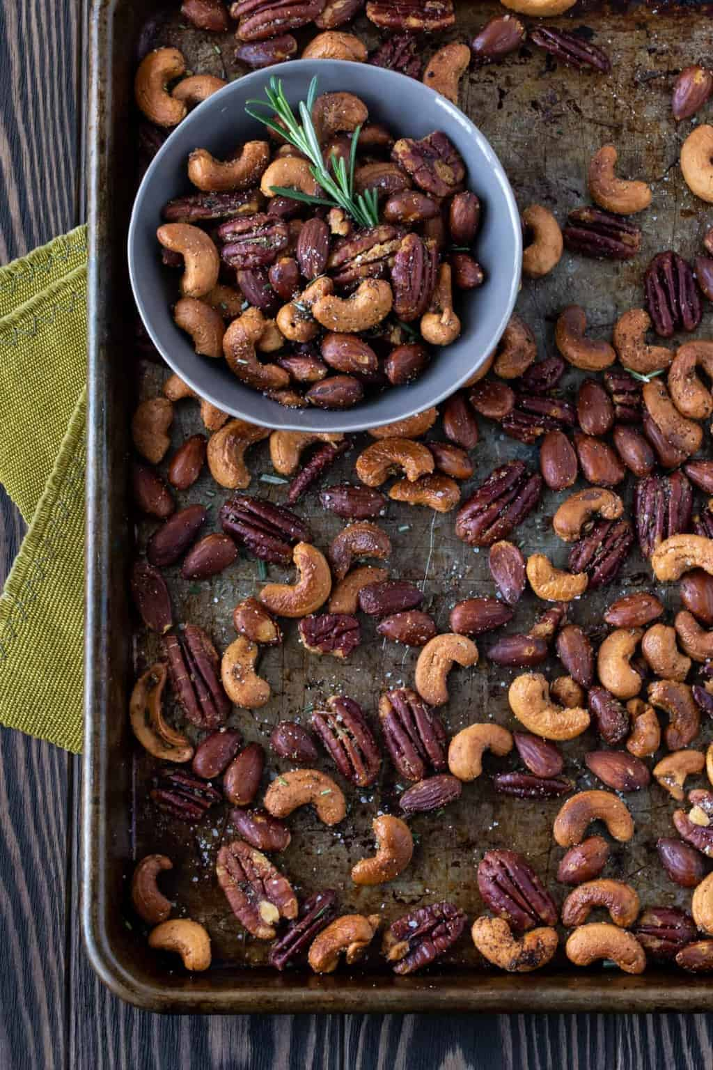Chipotle and Rosemary Roasted Nuts on a sheet pan with a small bowl filled with nuts.