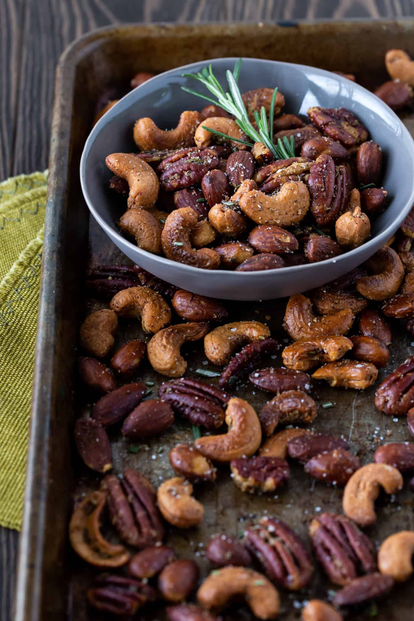 Chipotle Rosemary Roasted Nuts on a sheet pan with fresh rosemary for garnish.