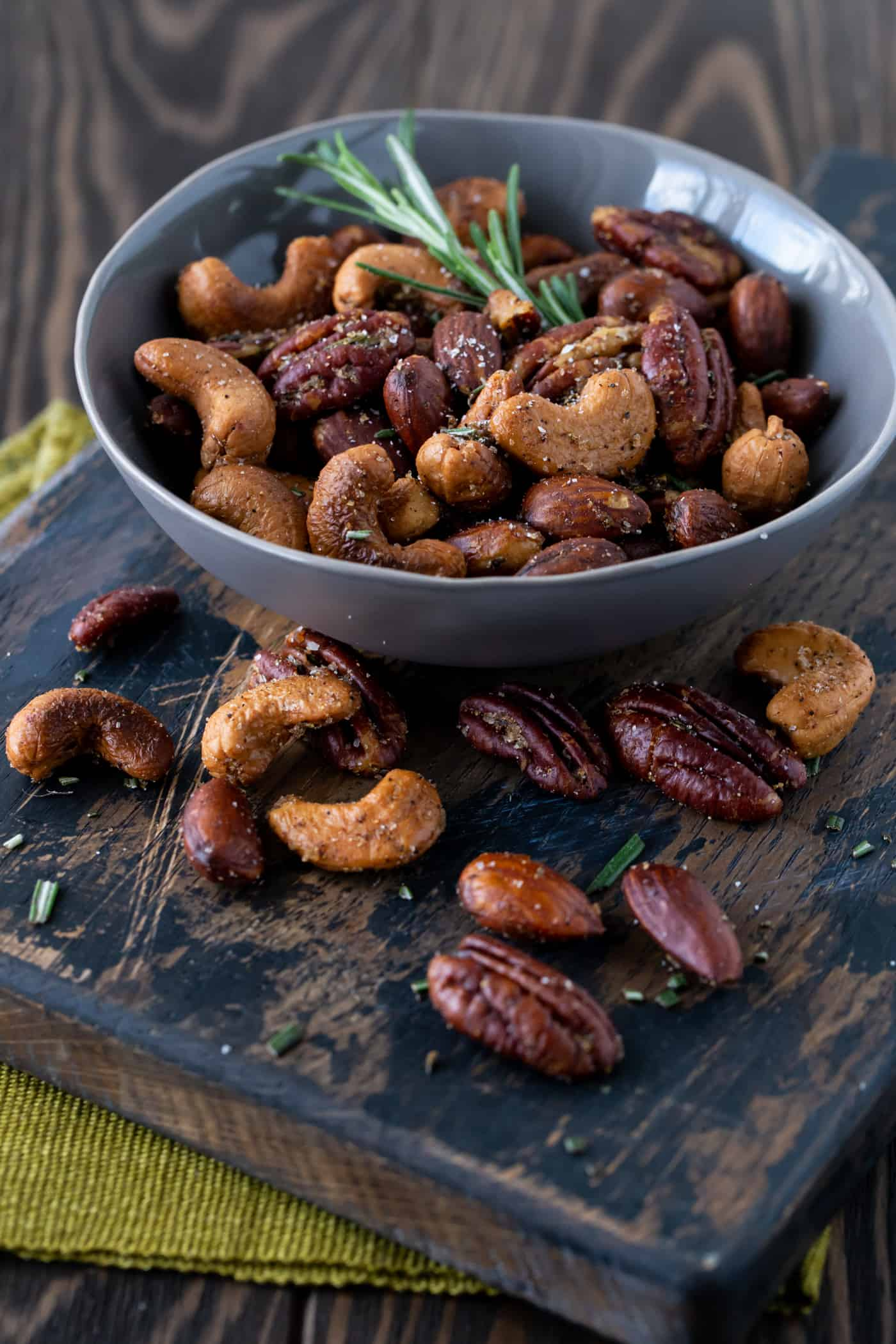 Serving bowl of Chipotle and Rosemary Roasted Nuts on a dark background with fresh rosemary for garnish.