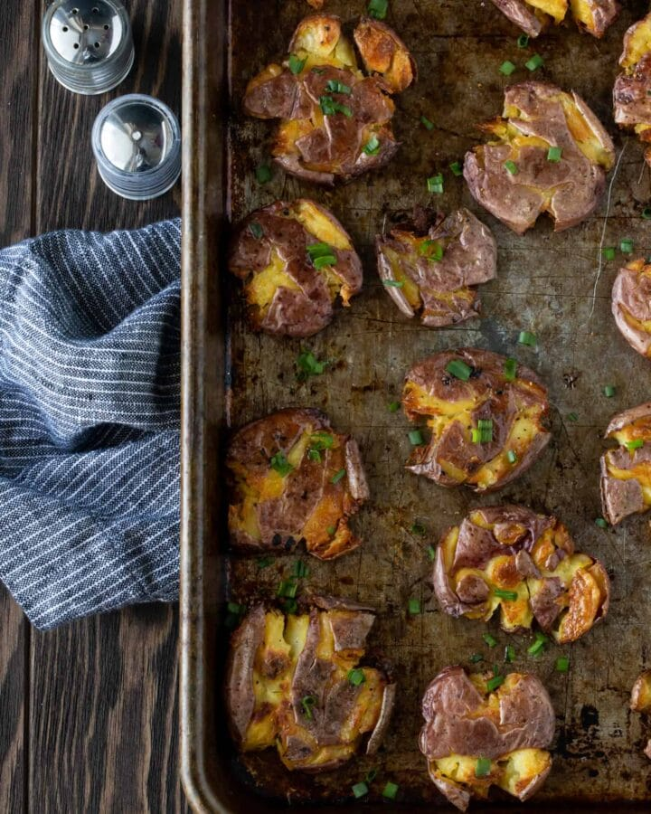 Top dowm image of Crispy smashed potatoes on a sheet pan.