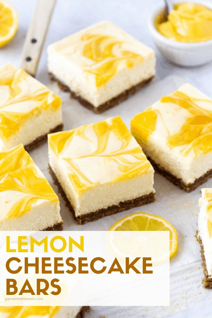 Lemon Cheesecake Bars on white parchment paper. A small bowl of fresh lemon curd is nearby. Garnished with fresh lemon slices.