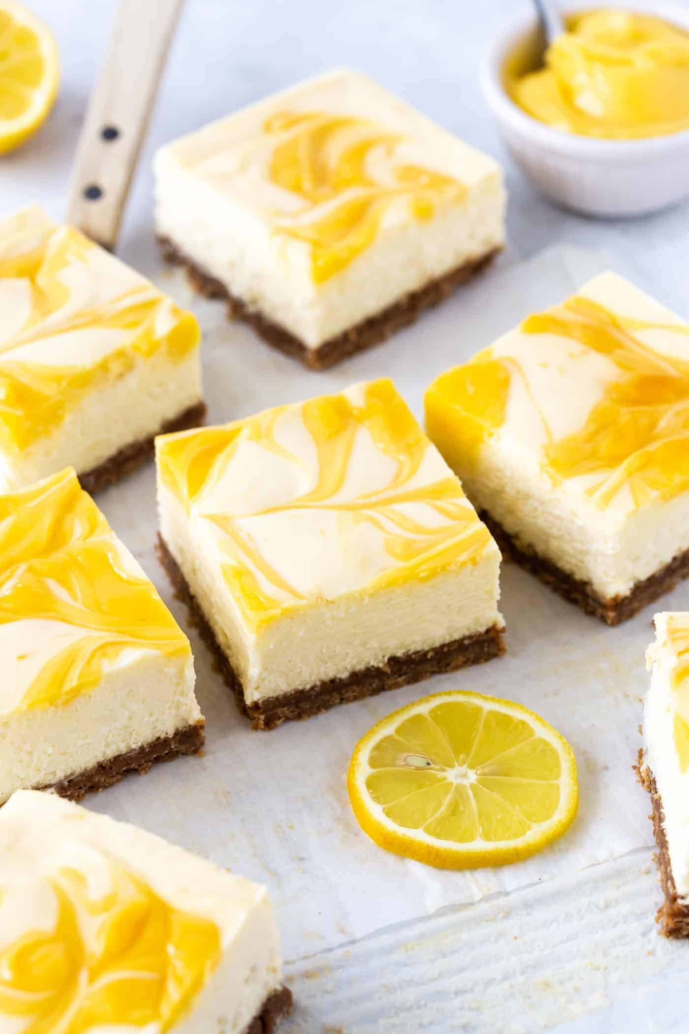 Cut Lemon Cheesecake Bars topped with swirled fresh lemon curd on white parchment paper.