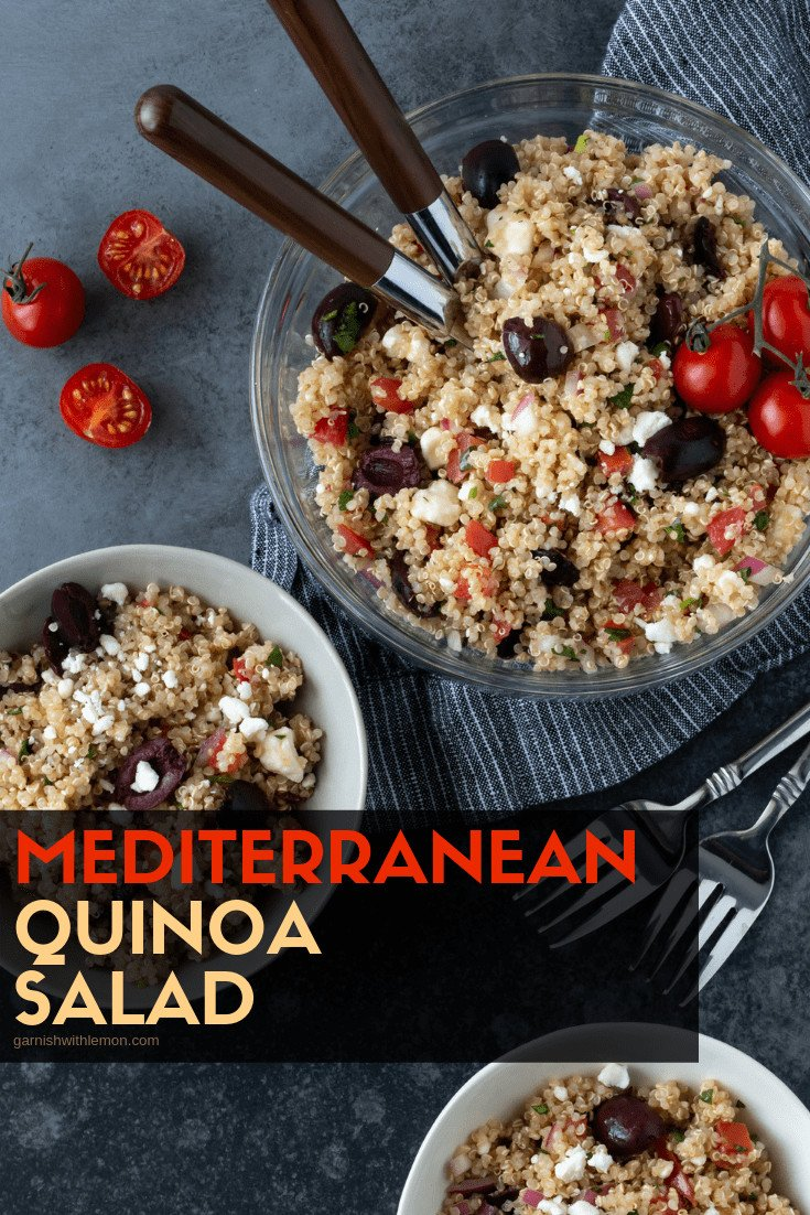 Close up of Mediterranean Quinoa Salad in a glass serving bowl on a dark grey background with wooden spoons for serving. Garnished with fresh cilantro and sliced tomatoes.