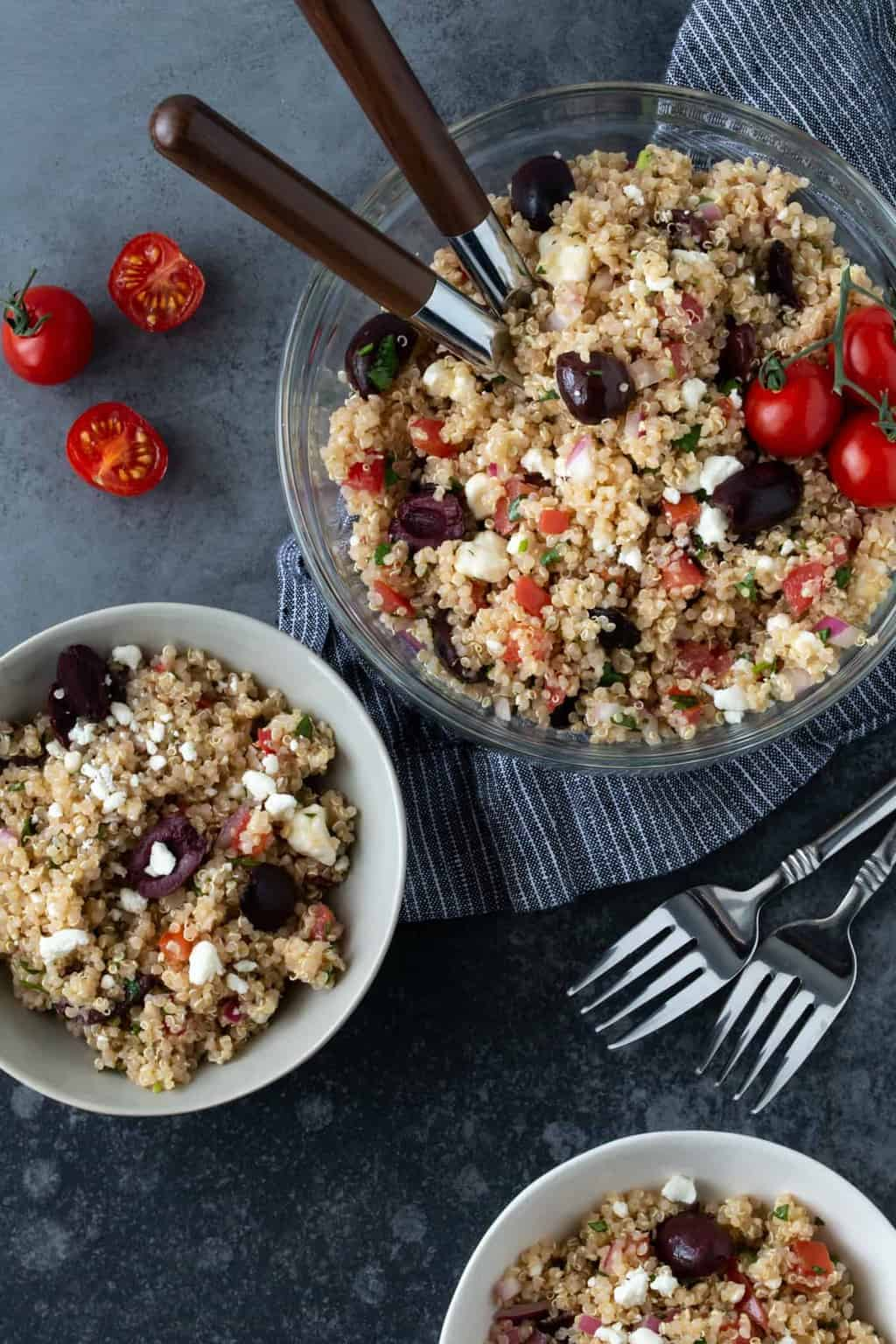 Mediterranean Quinoa Salad recipe in glass serving bowl with small bowl on side for eating.