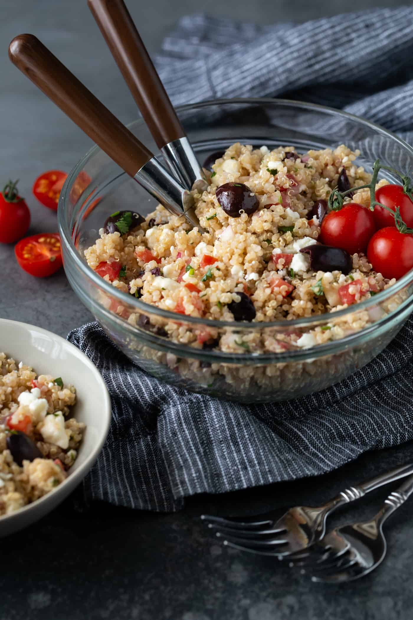 Mediterranean Quinoa Salad in a glass bowl on a dark background garnished with sliced grape tomatoes.