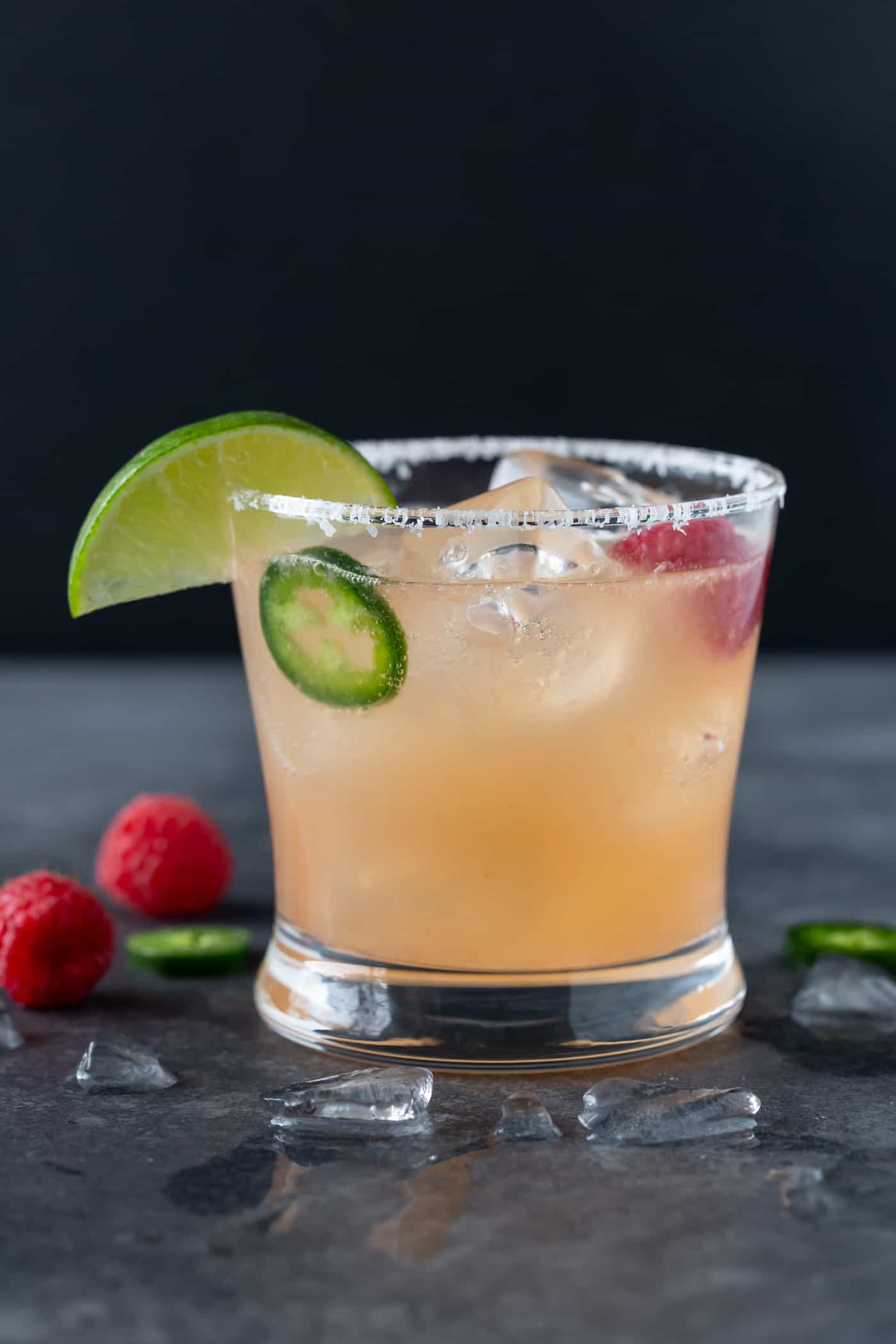 A lowball glass with a salted rim filled with Raspberry Paloma Cocktail and garnished with fresh raspberries, jalapeno slices and a lime wedge.