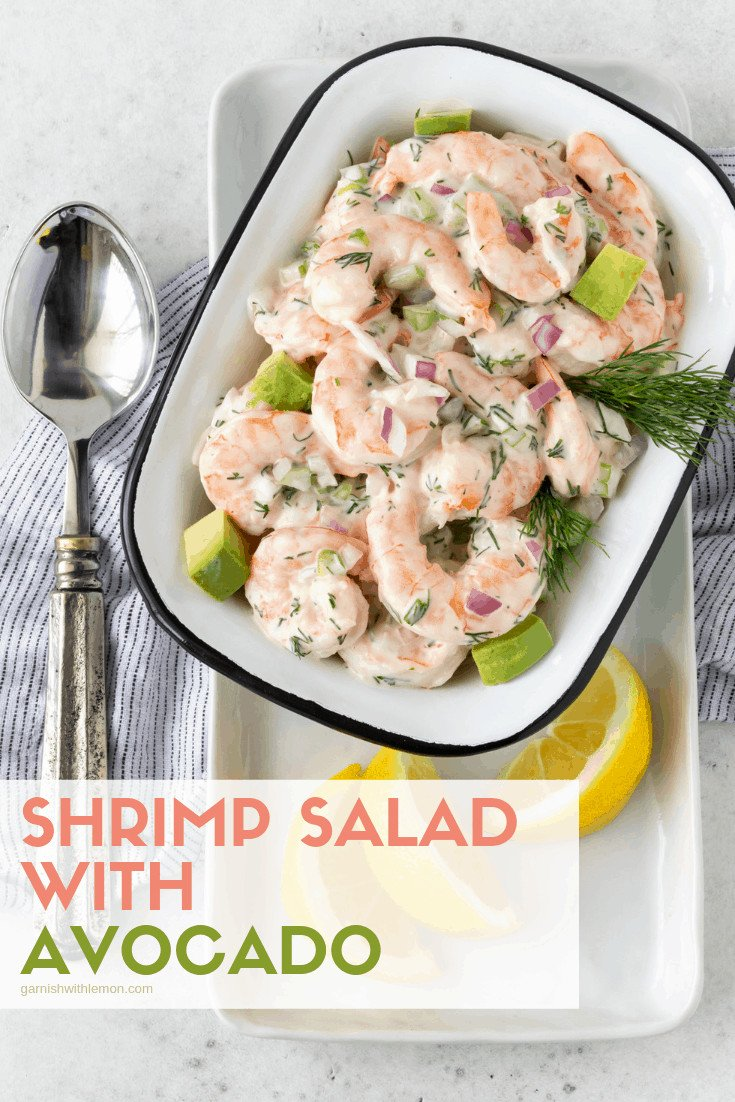 Shrimp Salad with Avocado in a white serving bowl garnished with fresh dill and lemon wedges.