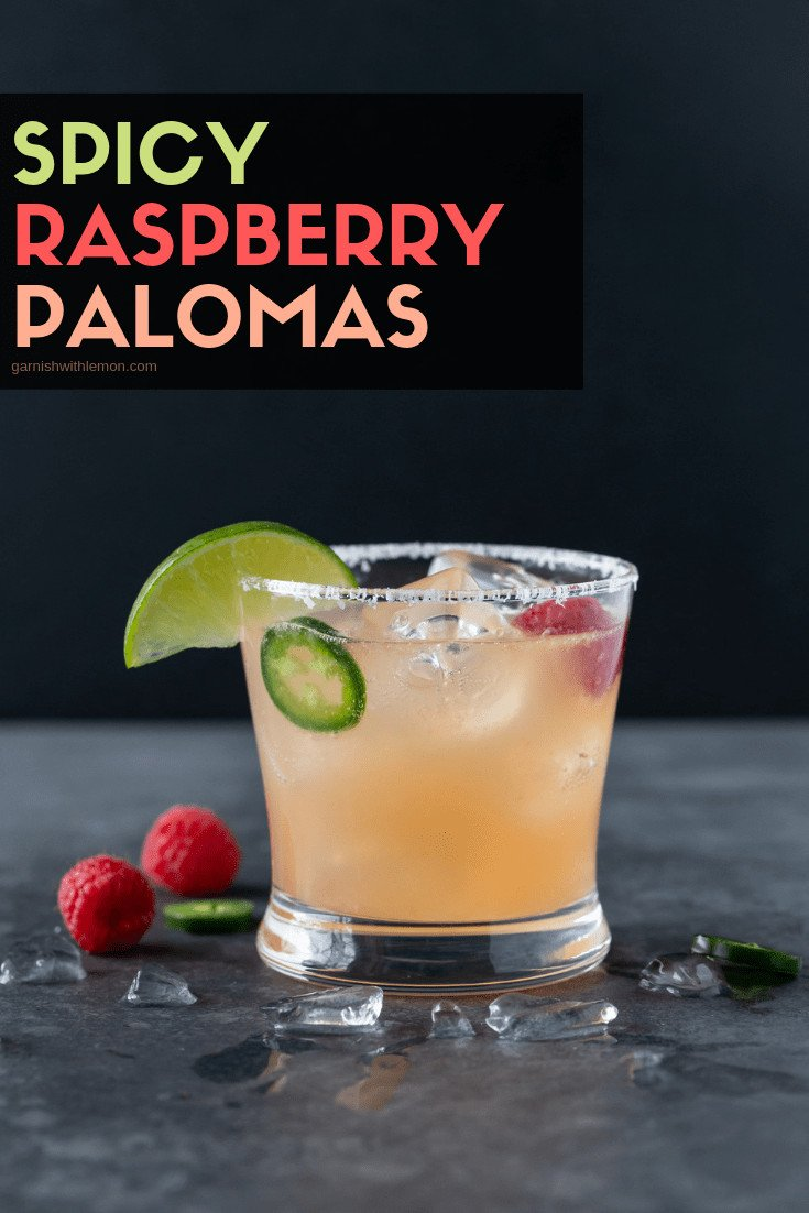 A single lowball glass with a salted rim is filled with Raspberry Paloma Cocktail and garnished with a lime wedge, fresh raspberries and jalapeno slices.