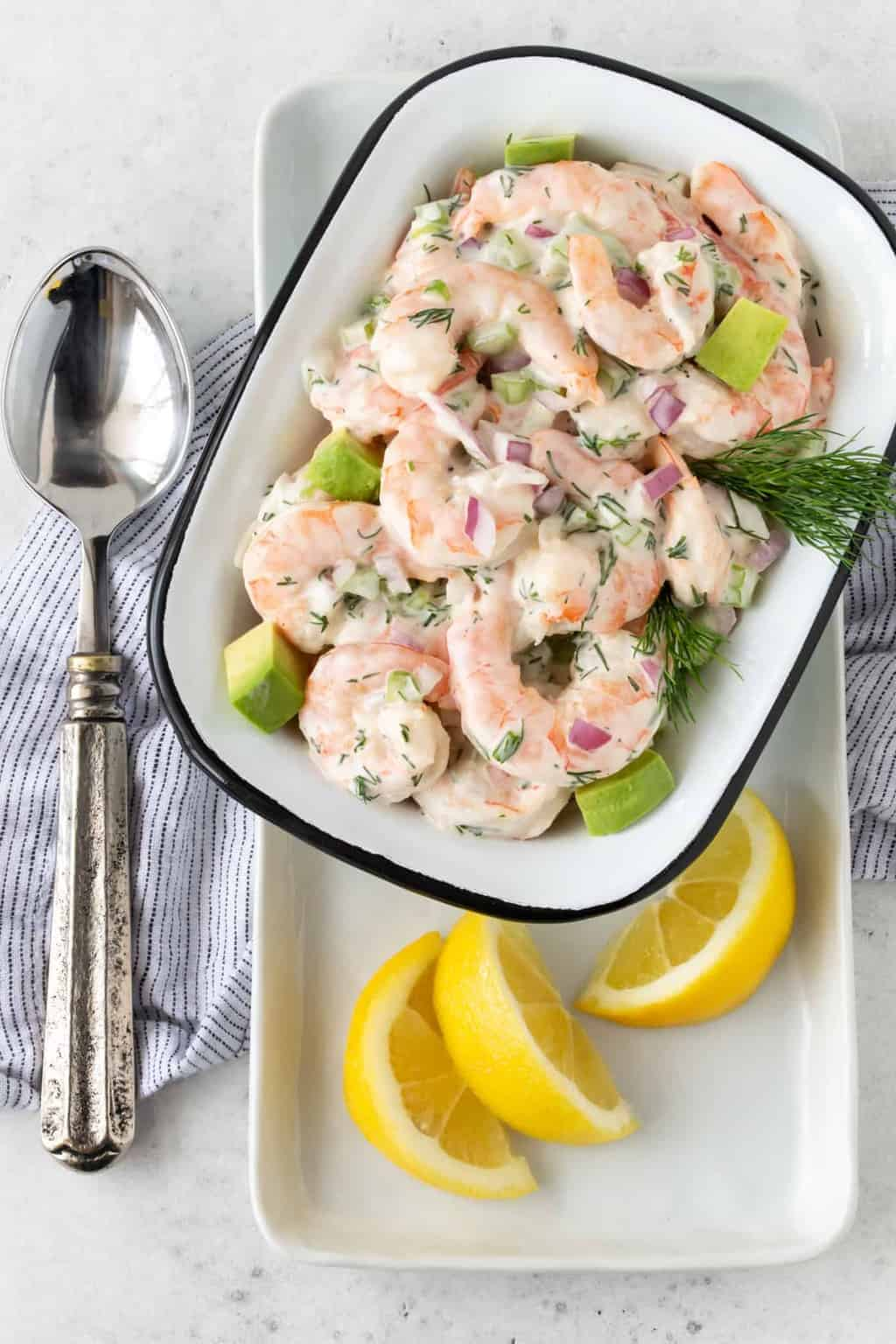 Top down image of Shrimp Salad with Avocado in a white serving dish with a silver spoon for serving and fresh lemon wedges for garnish.