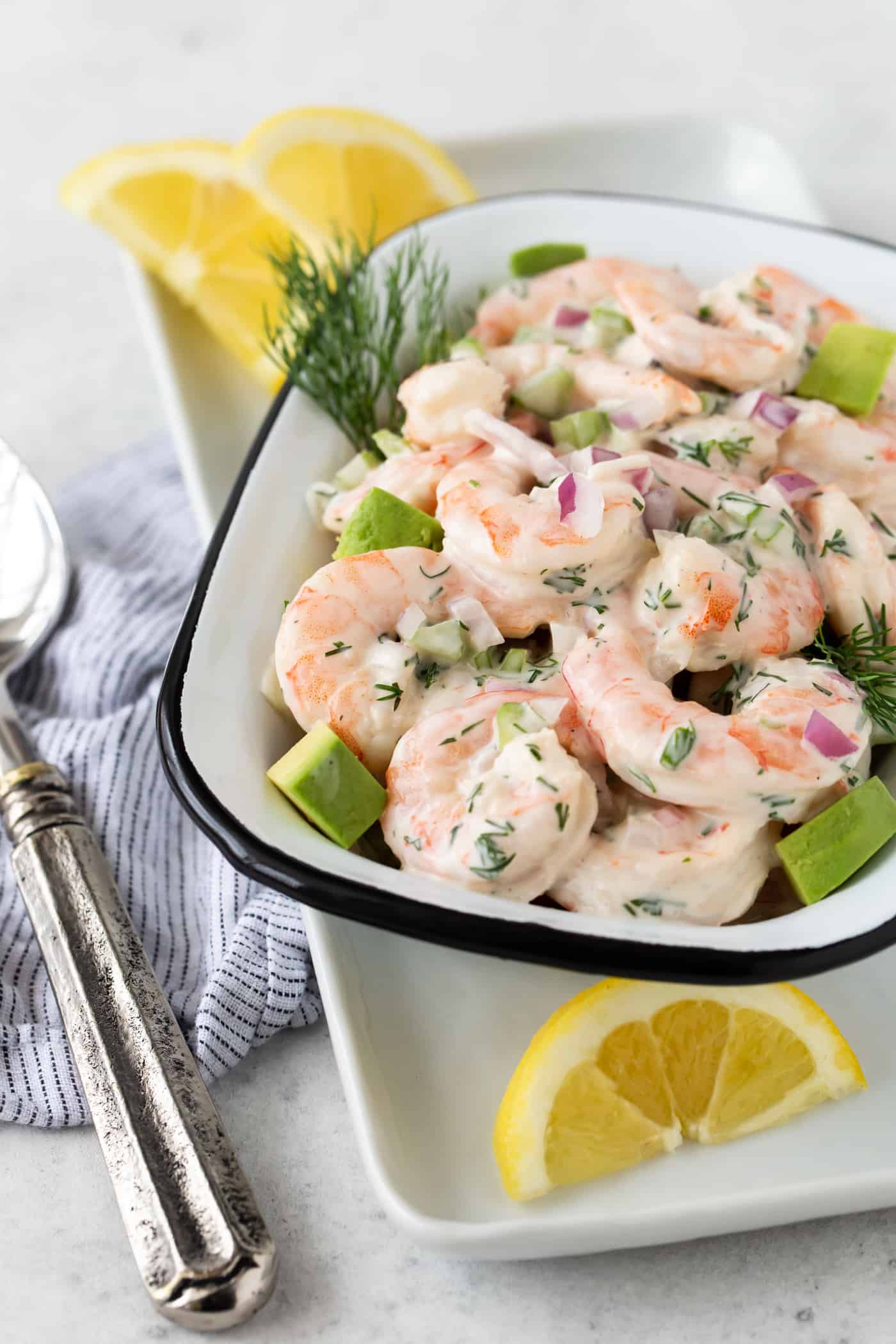 Shrimp Salad with Avocado in a white serving bowl with fresh dill and lemon wedges for garnish.
