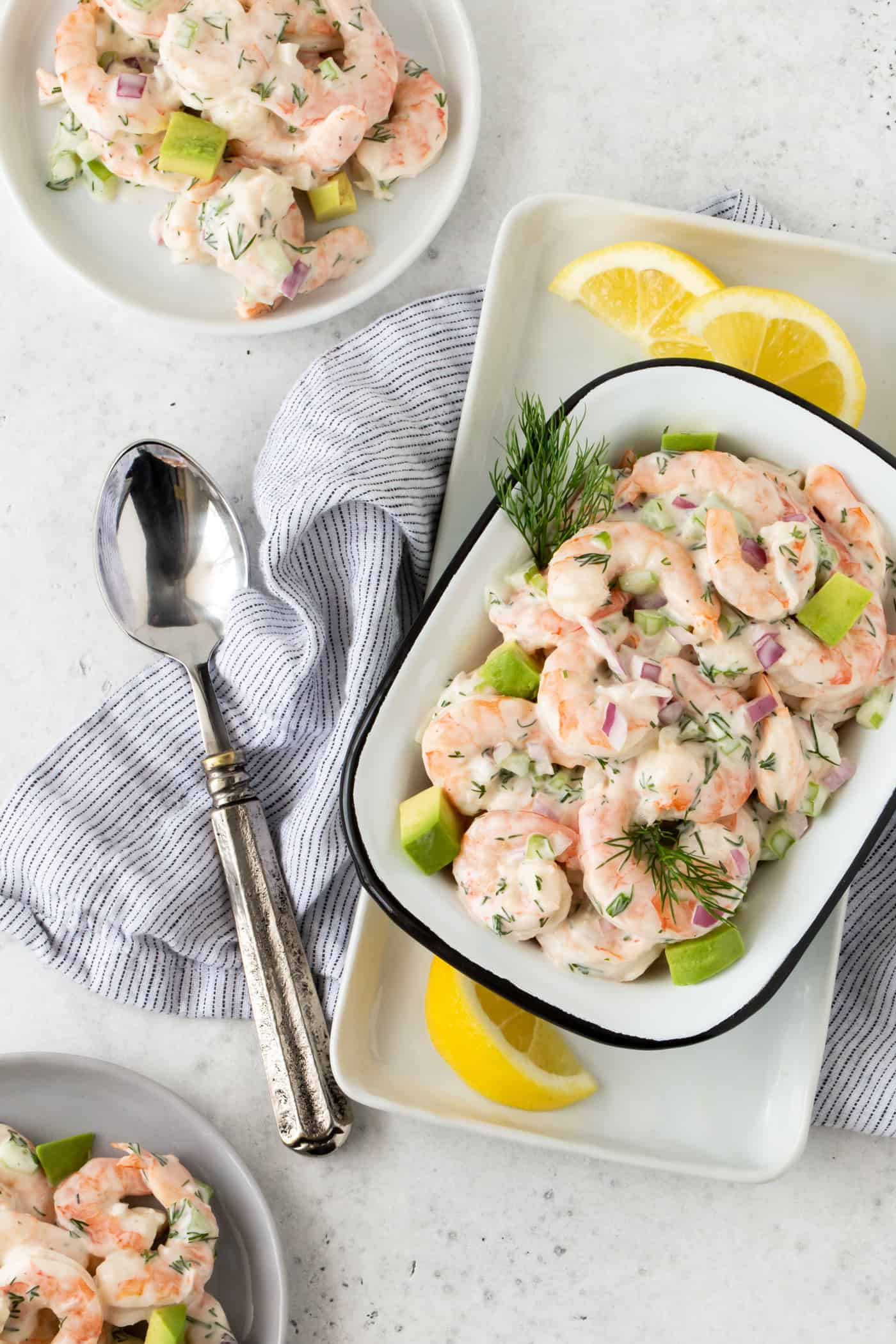 Shrimp Salad with Avocado in a white bowl with fresh dill and lemon wedges on a white surface.