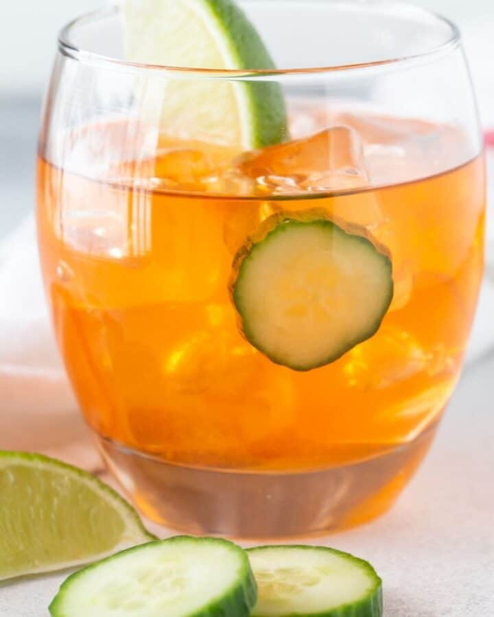 orange drink in glass with cucumber.