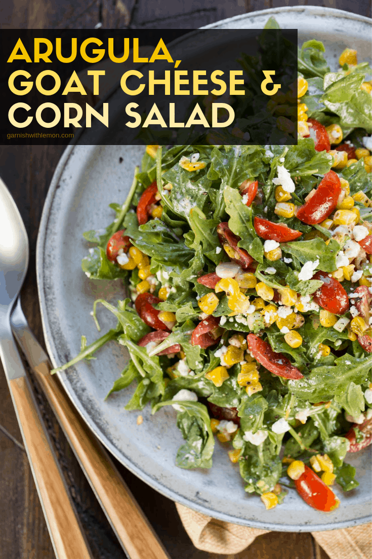 Arugula Goat Cheese Corn Salad on a silver plate garnished with fresh tomatoes.